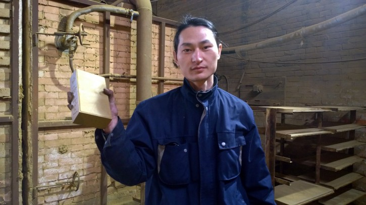 In this Monday, Nov. 30, 2015 photo, Chinese artist Wang Renzheng holds up a brick in Tangshan in northern China's Hebei province containing dust and pollutants Wang vacuumed from theair in Beijing. Wang spent 4 hours per day for 100 days vacuuming the Beijing air with an industrial shop-vac, then baked the accumulated dust and pollutants into a brick. (Wang Renzheng via AP)