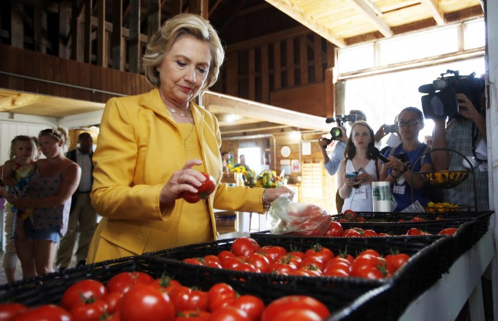 FILE - In this July 28, 2015, file photo, Democratic presidential candidate Hillary Clinton gets fresh tomatoes at Dimond Hill Farm between campaign stops in Hopkinton, N.H. Clinton knows from three previous trips down the presidential campaign trail, politicking means picking your food carefully. Since launching her campaign bid in April, Clinton has embarked on a rigorous diet plan, hoping to stave off the pounds that often accompany the near-sleepless nights and non-stop snacking of a campaign. (AP Photo/Jim Cole, File)