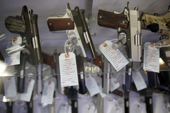 FILE - In this Nov. 15, 2014 file photo, handguns sit in a glass display case in Bridgeton, Mo. The FBI processed a record number of firearms background checks on Black Friday, the agency said Tuesday. (AP Photo/Jeff Roberson, File)