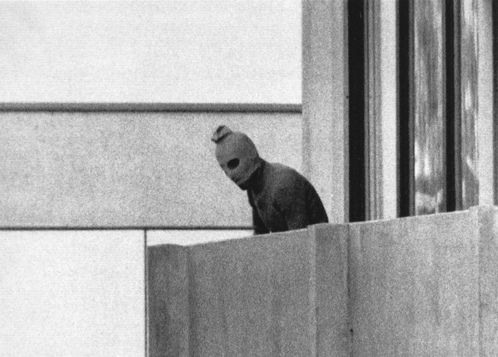 FILE - In this Sept. 5, 1972, file photo, a Palestinian gunman looks from an apartment in which were seized members of the Israeli Olympic Team at their quarters at the Munich Olympic Village.  (AP Photo/Kurt Strumpf, File)