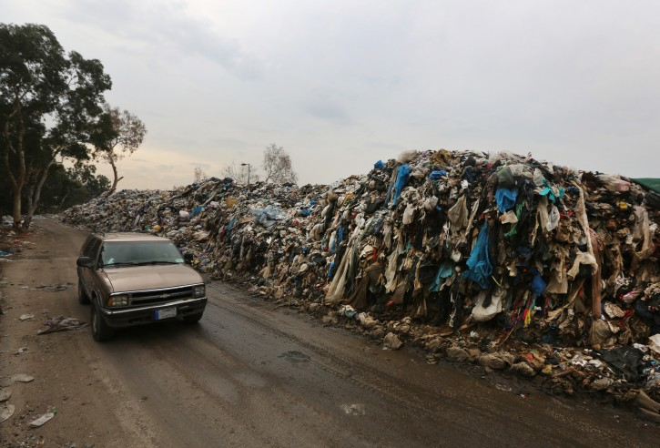 In this Thursday, Dec. 17, 2015 photo, a car passes by a pile of garbage in Karantina, east Beirut, Lebanon. Lebanon's trash collection crisis which set off summer protests is entering its sixth month, but you would hardly be able to know it in Beirut. (AP Photo/Bilal Hussein)