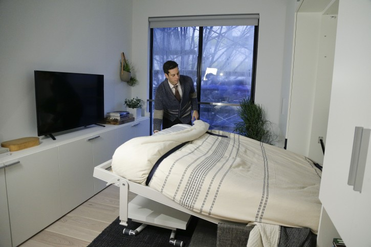 In this Dec. 22, 2015 photo, Stage 3 Properties co-founder Christopher Bledsoe demonstrates a retractable bed that turns into a sofa when stored inside one of the apartment units at the Carmel Place building in New York.  (AP Photo/Julie Jacobson)