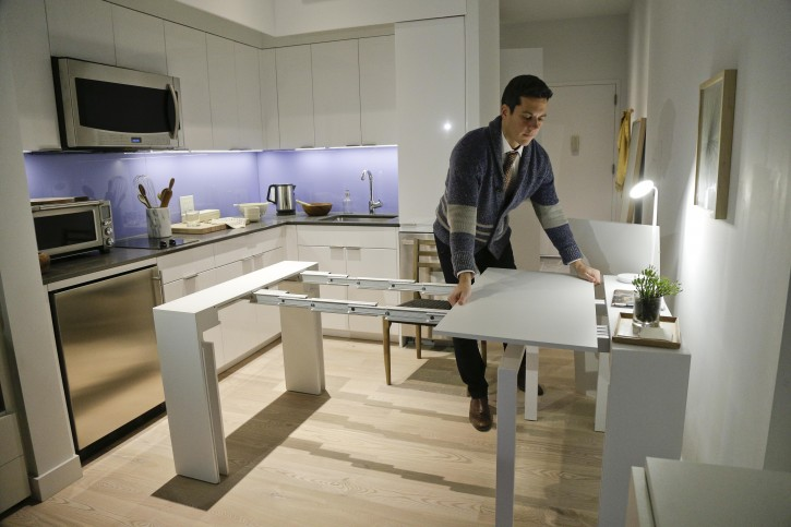 "In this Dec. 22, 2015, photo, Stage 3 Properties co-founder Christopher Bledsoe demonstrates a desk that expands into a dining table that can seat up to 12 people inside one of the apartments at the Carmel Place building in New York. As the city-sponsored ""micro-apartment"" project nears completion, it's setting an example for tiny dwellings that the nation's biggest city sees as an aid to easing its affordable housing crunch. (AP Photo/Julie Jacobson)"