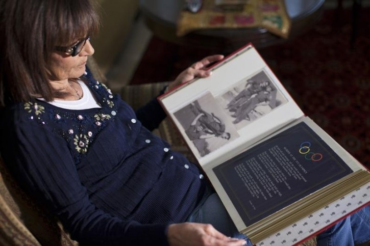 FILE  - Ilana Romano, widow of weightlifter Joseph Romano, holds an album with photos of her husband at her home in Tel Aviv February 28, 2012. Reuters