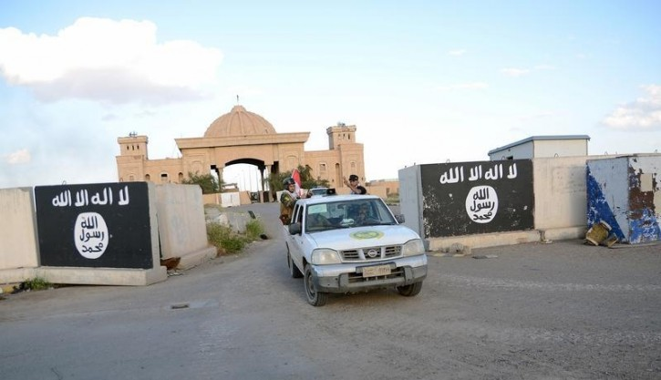 FILE - Shi'ite paramilitary fighters ride a vehicle past a wall painted with the black flag commonly used by Islamic State militants, with the palaces of former Iraqi president Saddam Hussein behind them, in Tikrit, March 31, 2015. Reuters