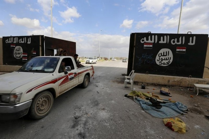 FILE - Shi'ite paramilitary fighters ride a vehicle past a wall painted with the black flag commonly used by Islamic State militants, near former Iraqi president Saddam Hussein's palace in Tikrit  April 1, 2015.  Reuters