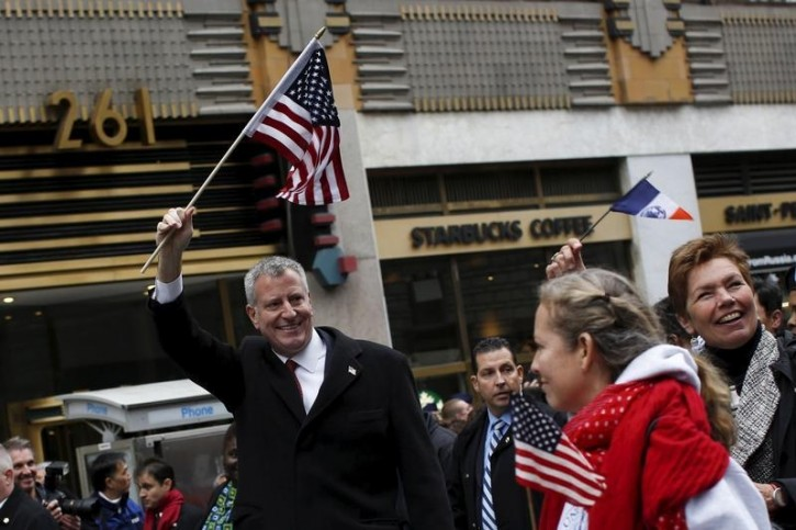 FILE - New York City Mayor Bill de Blasio waves a U.S. flag during the Veterans' Day parade in New York November 11, 2015. REUTERS/Shannon Stapleton