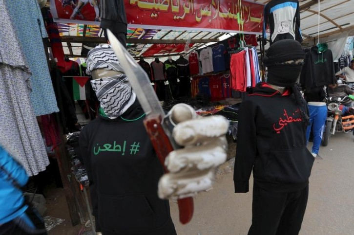 "FILE - A mannequin holding a knife displaying a jacket that reads ""stab"" (L) is seen outside a clothes shop in Khan Younis, in the southern Gaza Strip November 3, 2015. Reuters"