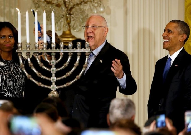 Israeli President Reuven Rivlin (C) lights a menorah as he joins U.S. President Barack Obama (R) for a Hanukkah reception at the White House in Washington December 9, 2015. Also pictured is U.S. first lady Michelle Obama (L).  REUTERS/Jonathan Ernst
