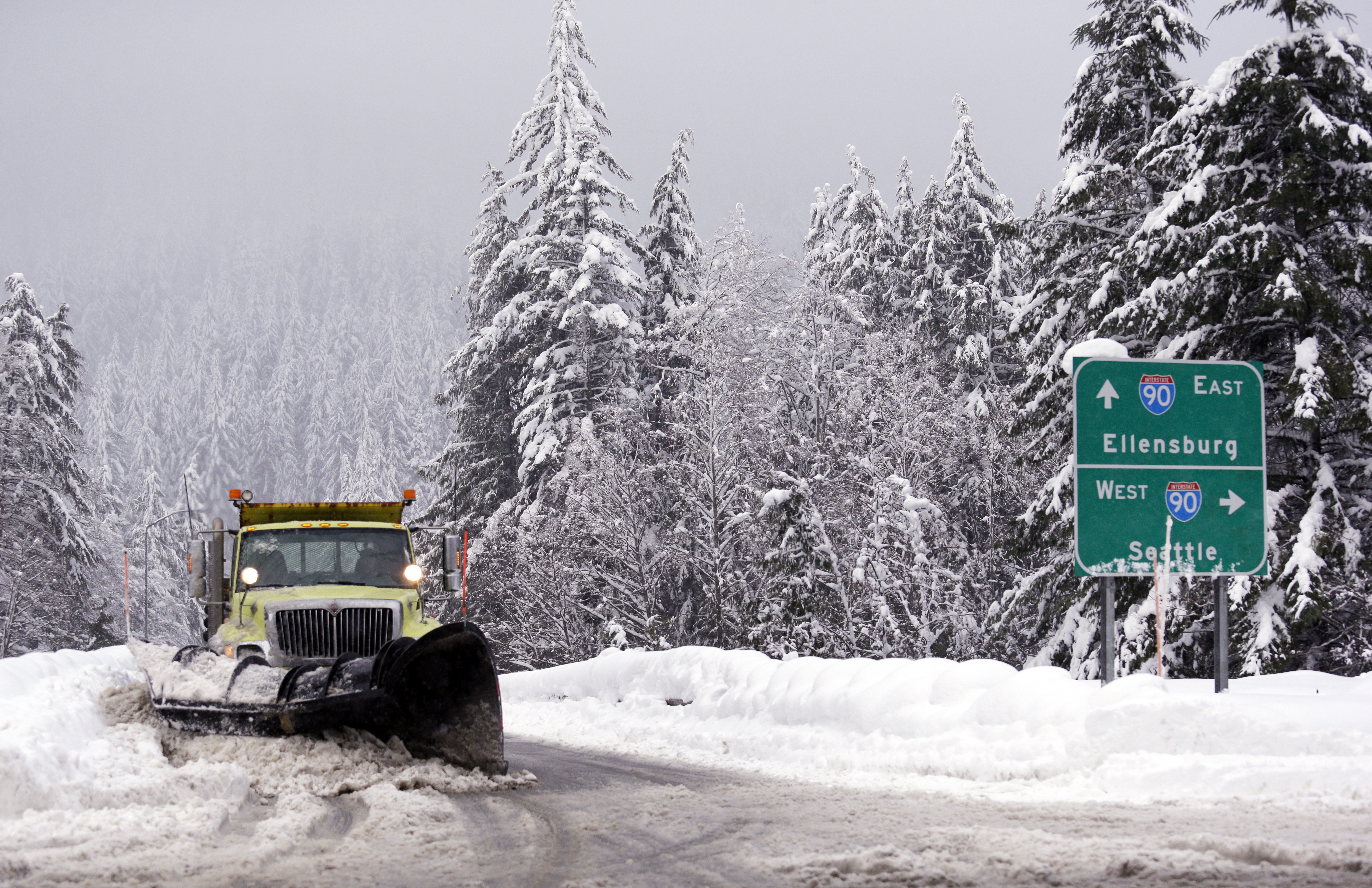 A snowplow clears an overpass of freshly-fallen snow over Interstate 90 at Snoqualmie Pass