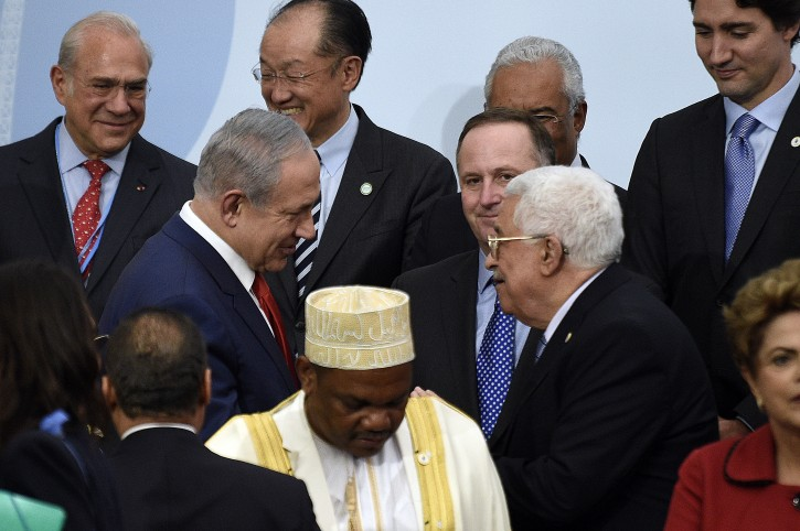FILE - Israeli Prime Minister Benjamin Netanyahu (C-L) talks with Palestinian President Mahmud Abbas (R)  in front of New Zealand's President John Key (C) during the family photo during the COP21, United Nations Climate Change Conference, in Le Bourget, outside Paris, France, 30 November 2015.