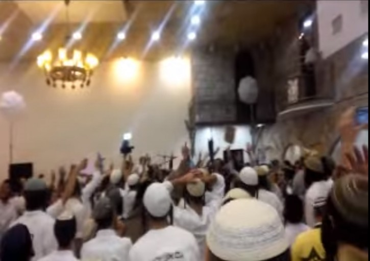 This still from the video of a wedding among right-wing activists shows dancers brandishing rifles, a twist on traditional wedding dances. (Screenshot)