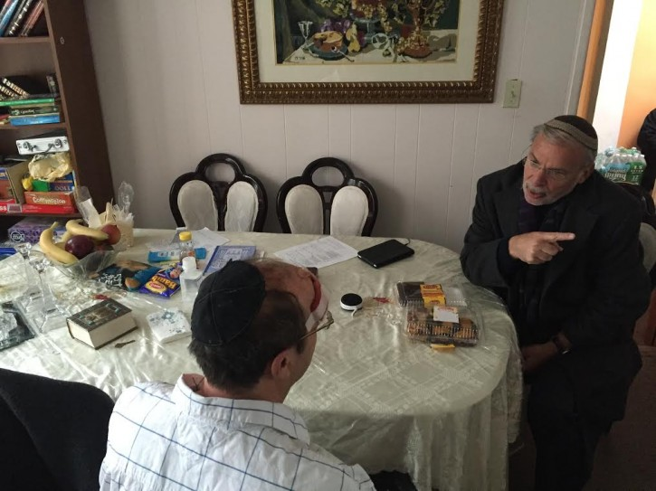 Assemblyman Dov Hikind (D-Brooklyn) sits with the Jewish victim of the Midwood attack at his home to reassure that the criminals will be apprehended. (Dov Hikind)