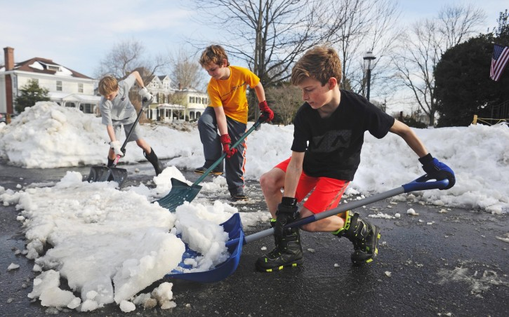 As temperatures push into the upper 50s, from left, Sam DuMont, Jake Wack, and Luke DuMont shovel a patch of snow and ice along Washington Avenue in Fredericksburg, Va.,  Tuesday, Jan. 26, 2016. (Peter Cihelka/The Free Lance-Star via AP)