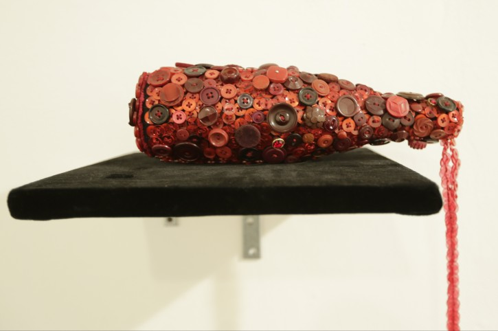 """""""A Harlem Hangover,"""" by Beau McCall simulating a spilled wine bottle, is on display for The Button Show at the Rush Arts Gallery Wednesday, Jan. 20, 2016, in New York. Clothing buttons are reimagined as an artistic medium in contemporary art in the show running through March 12. (AP Photo/Frank Franklin II)"""