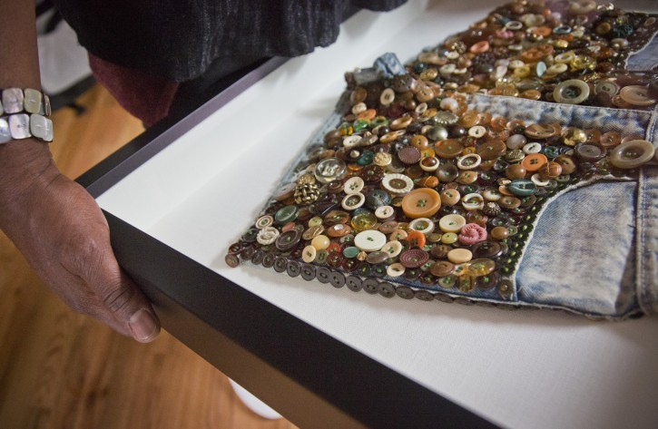 """Visual artist Beau McCall reveals """"Hot Fun in the Summatime 2,"""" a wearable art denim shorts he illustrated with buttons, Thursday, Jan. 14, 2016, in New York. McCall is among 11 artists appearing in """"The Button Show,"""" which opens at the Rush Arts Gallery in Chelsea on Jan. 22 and runs through March 12. (AP Photo/Bebeto Matthews)"""