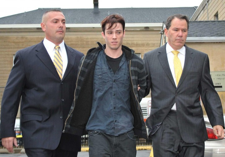 In this Oct. 19, 2012, photo, James Ryan, of Oakdale, N.Y., is escorted from Nassau County Police headquarters, in Mineola, N.Y., after his arrest on drunken driving charges. Prosecutors say that it was Ryan's accident that initiated a series of events that brought Nassau County Police Officer Joseph Olivieri to the scene: resulting in the officer's death. Olivieri was killed by an SUV that collided with the wreckage from Ryan's accident. (Howard Schnapp/Newsday via AP)