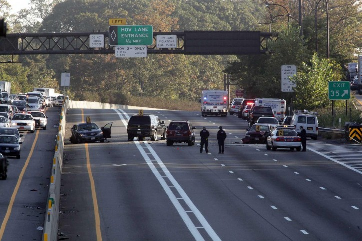 In this Oct. 18, 2012, photo, Nassau County police investigate the scene of a fatal accident on the Long Island Expressway in North Hills, N.Y., which left an officer dead. (Howard Schnapp/Newsday via AP)