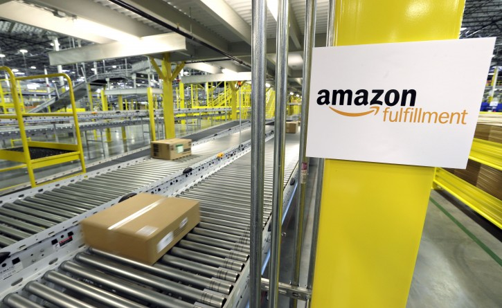 FILE - In this Feb. 13, 2015, file photo, a package moves along a conveyer belt during a media tour of the Amazon.com fulfillment center in DuPont, Wash. Amazon.com reports quarterly financial results Thursday, Jan. 28, 2016. (AP Photo/Ted S. Warren, File)