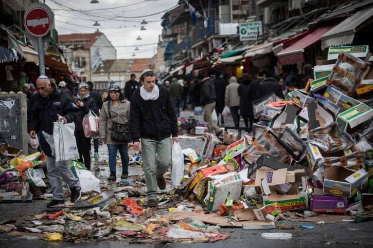 People walk next to a piles of garbage at the Mahane Yehuda Market in Jerusalem on January 3, 2016, on the 4th day of no garbage removal.  Flash90