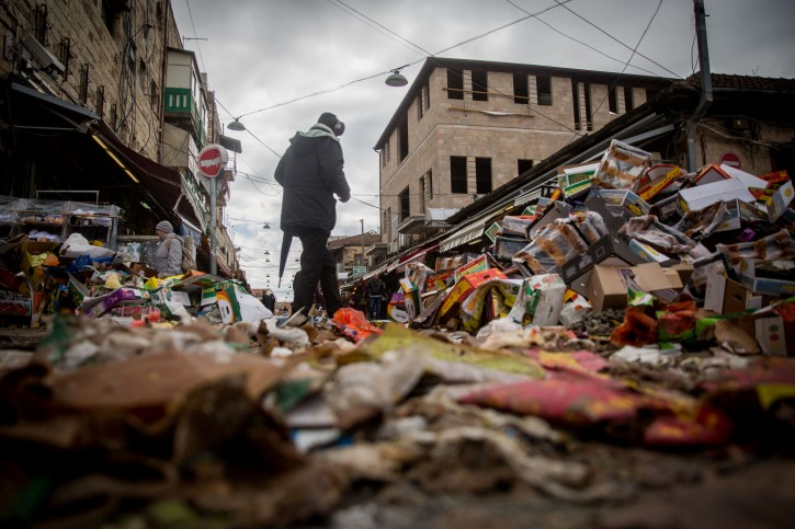 People walk next to a piles of garbage at the Mahane Yehuda Market in Jerusalem on January 3, 2016, on the 4th day of no garbage removal.