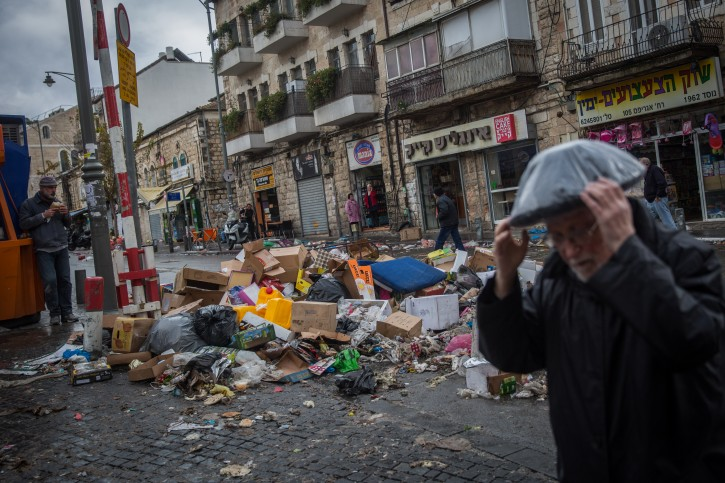 People walk next to a piles of garbage at the Mahane Yehuda Market in Jerusalem on January 3, 2016, on the 4th day of no garbage removal.. Flash90