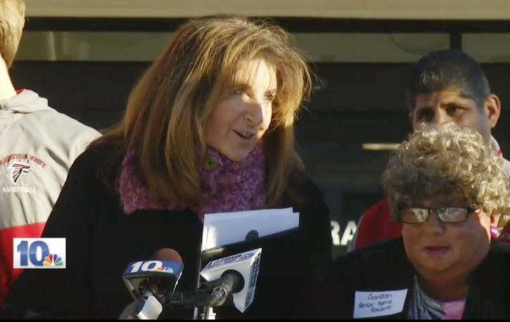 """In this Jan. 5, 2016 still image from WJAR-TV video, Sue Stenhouse, left, executive director of the Senior Enrichment Center, speaks alongside a man dressed as an elderly woman, right, during a news conference in Cranston, R.I., to promote a program for school children to help senior citizens shovel snow during the winter. The middle-aged male bus driver wore a wig, earrings, lipstick and a dress, and a tag that read, """"Cranston Senior Home Resident."""" Stenhouse resigned her position after the incident. (WJAR-TV via AP"""