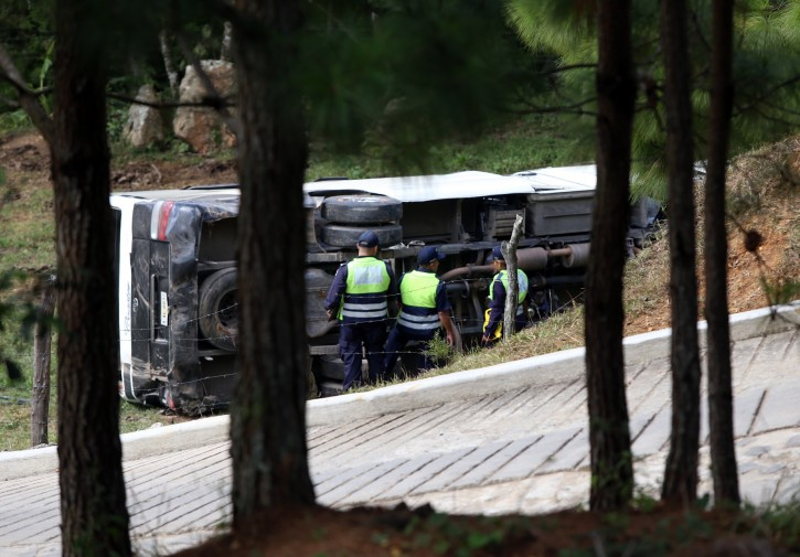This photo courtesy of El Heraldo de Honduras newspaper shows a bus on its side along the highway between the town of San Juancito and the capital city of Tegucigalpa, Honduras, Wednesday, Jan. 13, 2016. AP