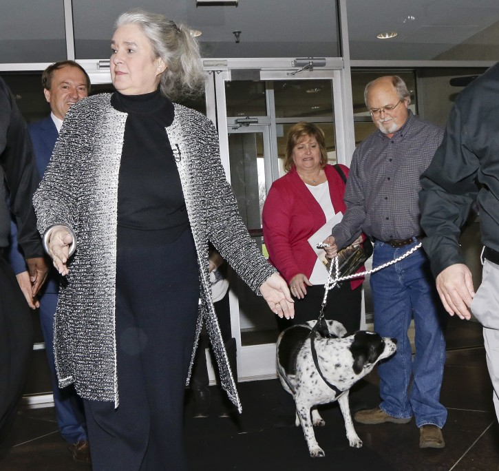 John Robinson, right, arrives at the Tennessee Lottery headquarters with his wife, Lisa, center, and family dog as Rebecca Hargrove, front left, president and CEO of the Tennessee Lottery, greets them Friday, Jan. 15, 2016, in Nashville, Tenn. The Robinsons claim to have one of the winning tickets in the record $1.6 billion jackpot drawing that took place Wednesday. (AP Photo/Mark Humphrey)