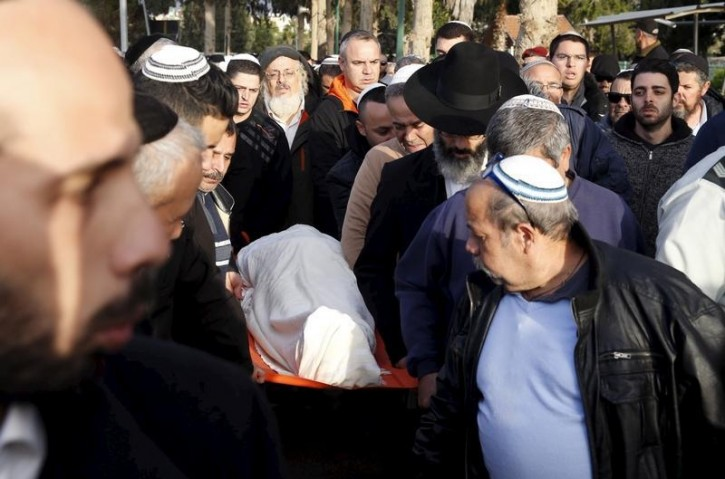 Mourners carry the covered body of Shimon Ruimi, who was killed in Friday's deadly shooting attack at a Tel Aviv bar, during his funeral in the southern Israeli town of Ofakim, January 3, 2016.  REUTERS/Baz Ratner