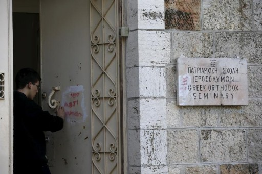 An Orthodox monk cleans graffiti from a door of the Greek Orthodox Seminary, located next to the Domition Abbey on Mount Zion in Jerusalem's Old City January 17, 2016. REUTERS