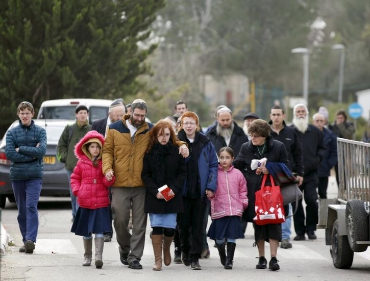 The husband and children of Dafna Meir, 38, walk together upon their arrival to her funeral ceremony in the West Bank Jewish settlement of Otniel January 18, 2016. Reuters