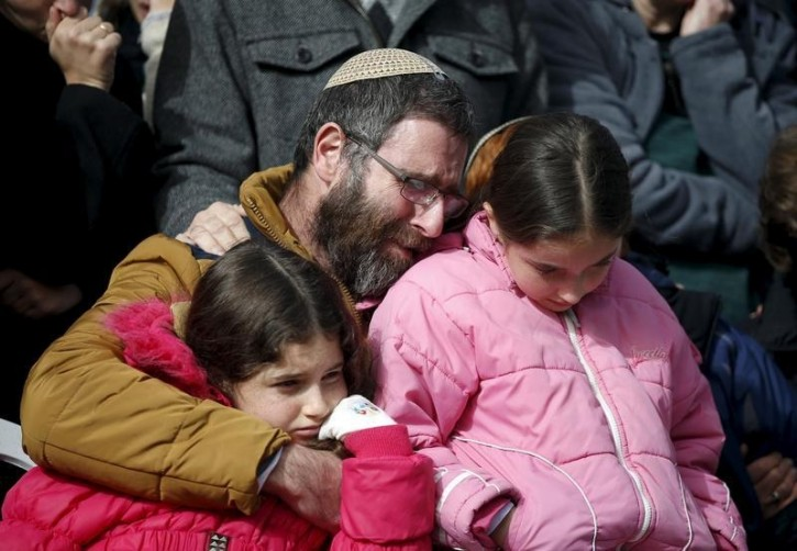 The husband and daughters of Dafna Meir, 38, mourn during her funeral at a cemetery in Jerusalem January 18, 2016. Meir, a female resident of the West Bank Jewish settlement of Otniel, was stabbed to death in her home on Sunday when an assailant broke into her house and attacked her, the Israeli army and a local settlement official said. REUTERS/Ronen Zvulun