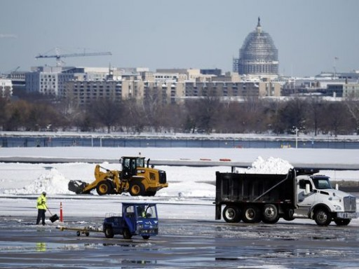 Workers remove snow on the tarmac at Ronald Reagan National Airport, with the U.S. Capitol dome seen behind, Sunday, Jan. 24, 2016 in Arlington, Va. Millions of Americans began digging out Sunday from a mammoth blizzard that set a new single-day snowfall record in Washington and New York City. (AP Photo/Alex Brandon) (Photo: Alex Brandon / AP)