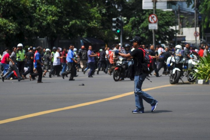 A man is seen holding a gun towards the crowd in central Jakarta, Indonesia, in this picture provided to Reuters by Xinhua News Agency January 14, 2016. REUTERS/Veri Sanovri/Xinhua