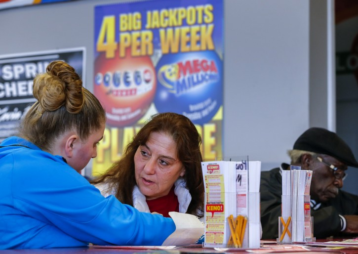 Donna Harris (R) consults with her daughter Stephanie Andrews while filling out play slips to purchase tickets for the multi-state Powerball lottery at Robinson's convenience store in Tallapoosa, Georgia, USA, 06 January 2016.  EPA
