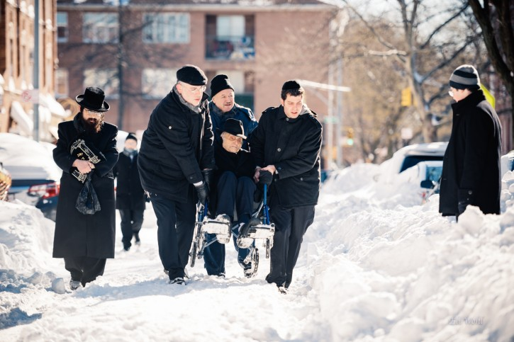 Holocaust Survivor Binyomin Jakubovic, being helped during the snowstorm on Jan. 24, 2016. Jakubovic a Borough Park resident for over 60 years who is currently over 90 years old and one of the oldest living survivors of Auschwitz. (Eli Wohl/VINnews.com)