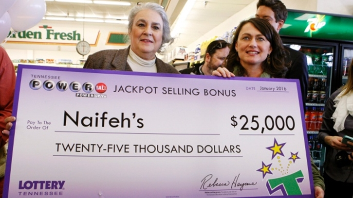Rebecca Hargrove, left, president & CEO of the Tennessee Lottery, presents a check to Dana Naifeh, right, owner of Naifeh's Grocery in Munford, Tenn., Thursday, Jan. 14, 2016. One of the winning Powerball tickets in Wednesday's record jackpot drawing of $1.6 billion was sold at the store. (AP Photo/Karen Pulfer Focht)