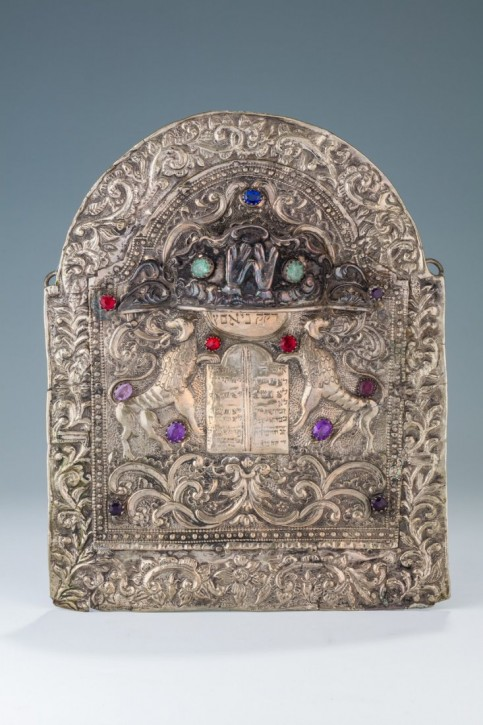 "PROPERTY OF ALAN DERSHOWITZ -- A RARE AND IMPORTANT SILVER TORAH SHIELD. Poland, 1802. Chased with two outwardly facing lions flanking a heavily inscribed Decalogue. The inner shield mounted onto a large frame. With a later added crown. 11"" tall. Estimate $12,000 -  $15,000"