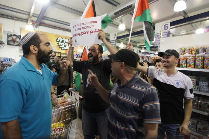 Foreign and Palestinian activists hold Palestinian flags as they march through a Rami Levy supermarket in the West Bank against Jewish settlements and in a call to boycott settlement products. Photo by Issam Rimawi/FLASH90 October 24, 2012.  Some 50 activists marched through the supermarket and tried to block a road in the settlement on Wednesday during a protest