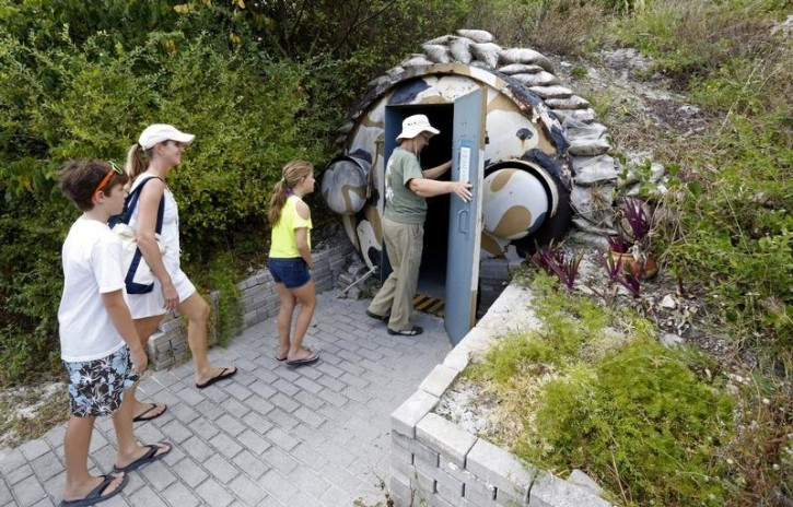 FILE  -Guests, led by curator Ruth Pelletier (R), enter the cold-war era nuclear fallout shelter constructed for U.S. President John F. Kennedy on Peanut Island near Riviera Beach, Florida November 8, 2013.  Reuters