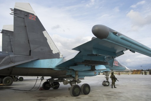 A Russian soldier stands guard next to a Su-34 bomber at Hemeimeem air base in Syria on Wednesday Jan. 20, 2016. (AP Photo/Vladimir Isachenkov)