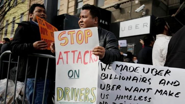 Uber drivers, including Bikash Tamang, center, participate in a rally in front of an Uber office in New York, Monday, Feb. 1, 2016. Some Uber drivers in New York City say they are going on strike to protest the company's decision to cut fares in the city by 15 percent. (AP Photo/Seth Wenig)