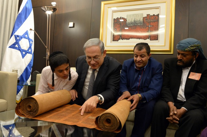 FILE - Israeli Prime Minister Benjamin Netanyahu looks at an 800 hundred years old torah scroll as he meets with Yemenite jews who were brought to Israel earlier this morning as part of a secret rescue operation, at the Knesset, the Israeli parliament in Jerusalem, March 21, 2016. Photo by Haim Zach/GPO