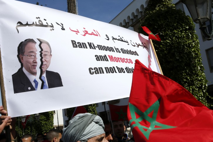 """Protesters hold a banner and the Moroccan flag as they chant slogans during a rally, in Rabat, Morocco, Sunday, March 13, 2016. Morocco has accused U.N. Secretary-General Ban Ki-moon of """"abandoning neutrality, objectivity and impartiality"""" during a recent visit to Western Saharan refugee camps in southern Algeria. (AP Photo/Abdeljalil Bounhar)"""