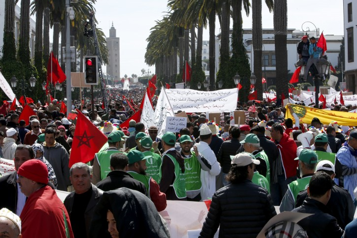 """Protesters hold banenrs and Moroccan flag as they chant slogans during a rally, in Rabat, Morocco, Sunday, March 13, 2016. Morocco has accused U.N. Secretary-General Ban Ki-moon of """"abandoning neutrality, objectivity and impartiality"""" during a recent visit to Western Saharan refugee camps in southern Algeria. (AP Photo/Abdeljalil Bounhar)"""