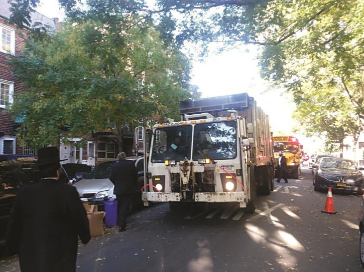 in this file photo a School bus is seen behind a NYC Sanitation truck on the streets of Borough Park (Hikind office)