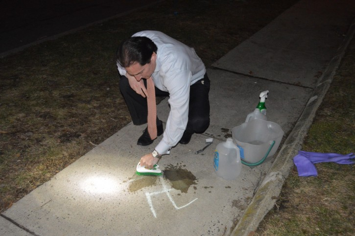 FILE - Assemblyman Todd Kaminsky washing the swastika from a sidewalk in Cedarhurst Mar. 7, 2016.