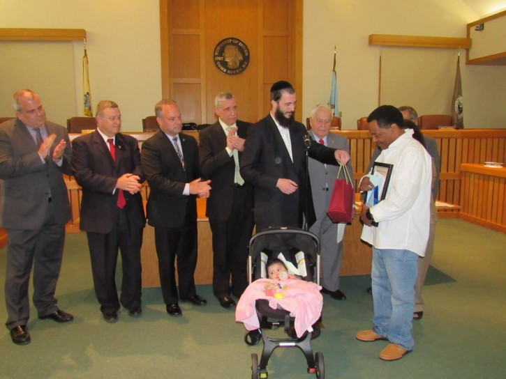 Dovid Eisdorfer, with his daughter in the ceremony in her stroller presenting William Copes with a gift.