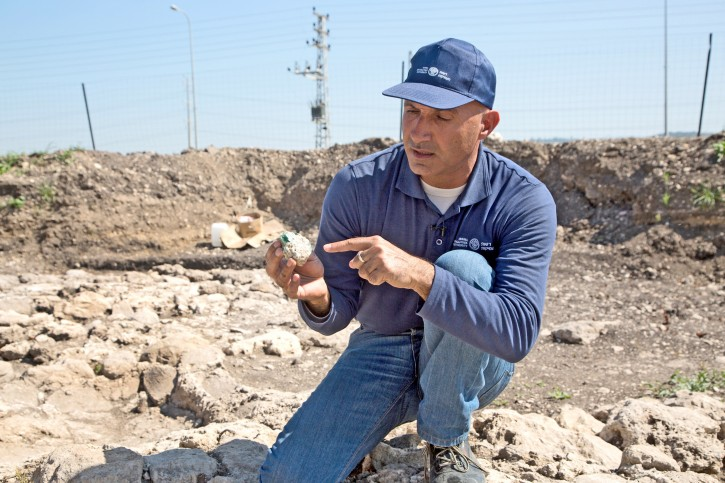 Excavation director Abdel Al-Salam Sa'id examining one of the glass chunks found in the area. (Shmuel Magal/Israel Antiquities Authority)